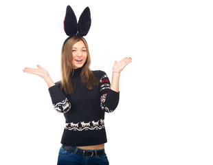Funny girl in a bunny suit. A woman in a winter sweater. Beautiful girl on a white background. Winter concept of advertising information. Christmas mood.