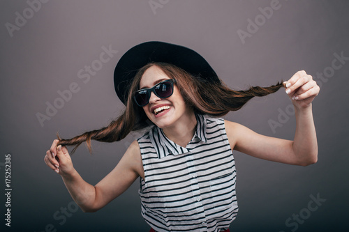 5de2164daaf Young beautiful fashionable woman with trendy makeup in black hat and  glasses on the grey background . Model looking at camera