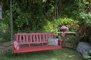 Rote Schaukelbank in einem Garten