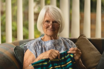 Senior woman knitting wool in living room