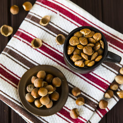 hazelnuts in a clay mug with shell around on a wooden table and striped towel