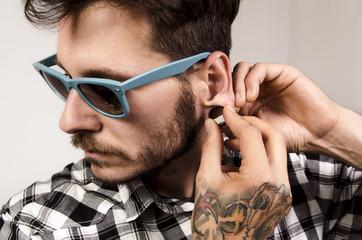 Closeup of handsome macho, tattooed man putting gauge earring, piercing