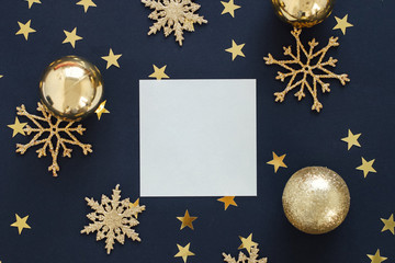 Mock up greeting card on black background with Christmas decorations ornaments glitter snowflakes, baubles and gold stars confetti. Invitation, paper. Place for text flat lay