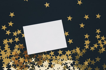 Christmas mock up greeting card on black background with gold stars confetti. Invitation, paper. Place for text flat lay