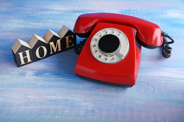 Red retro telephone with word home on blue wooden table