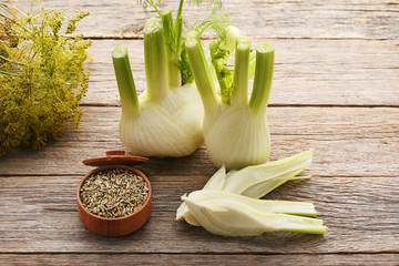Ripe fennel bulbs and dry seeds in bowl on grey wooden table