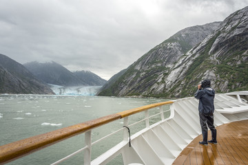 Cruise ship visitor taking photo of a big glacier in Glacier bay national park, Alaska