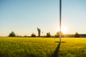 Full length view of the silhouette of a male player hitting a long shot on the putting green, of a professional golf course of a modern country club