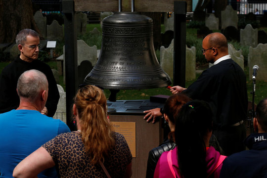People gather to ring the Bell of Hope, which is rung to remember victims of terrorism and violence around the world, to honour those killed and injured in the Las Vegas mass shooting, at St. Paul's Chapel in New York