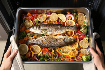 Papiers peints Poisson Woman taking baking tray with fish and vegetables out of oven