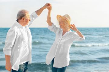 Happy senior couple walking at sea