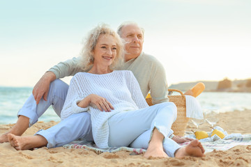 Happy senior couple having picnic on sea beach