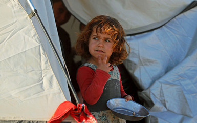 A girl holds an empty metal plate inside a refugee camp for people displaced by fightings between the Syrian Democratic Forces and Islamic State militants in Ain Issa