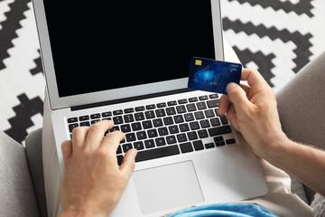 Man holding credit card while using laptop