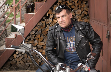The biker sits on a motorcycle in the yard of his house