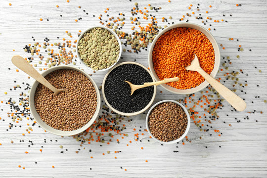 Bowls with different types of lentils on wooden table