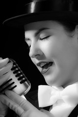 Young woman wearing top hat and singing into microphone.