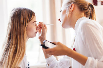 "Professional makeup artist working with beautiful young woman in white T-shirt with word ""less"""