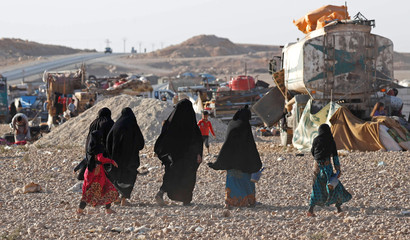 Displaced residents walk inside a refugee camp for people displaced by fightings between the Syrian Democratic Forces and Islamic State militants in Ain Issa
