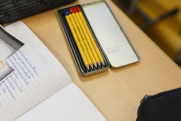 View of pencils and notebook in the classroom on the wooden table