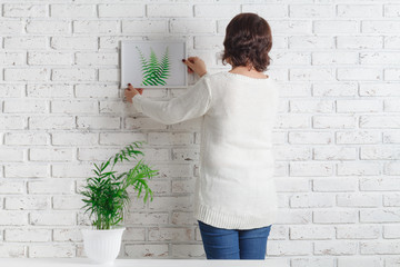 woman Putting Photo Frame On White Wall against the background of a houseplant