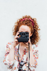 Young redhaired woman holding instant camera