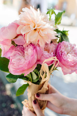 Someone holding a dahlia & garden rose arrangement.