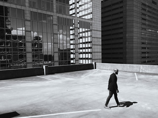 Mobile capture of A business man walking alone on a rooftop outdoor parking garage.