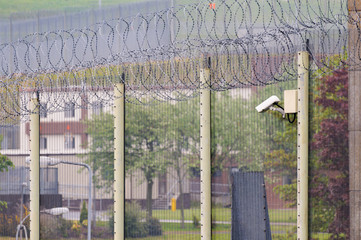 Prison fence with coiled razor wire and CCTV Cameras