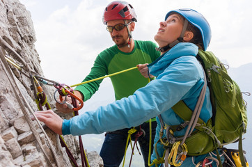 Rock climbers on the cliff regroup and check their climbing equipment