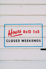 hand lettered sign showing business hours