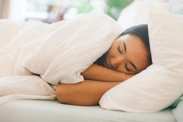 Side view of a young asian woman sleeping in white bed.