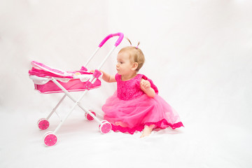 little beautiful girl dressed in pink dress playing with pink toy carriage on white isolated background