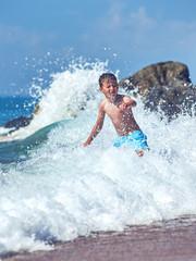 Cute Caucasian boy in sea waves.