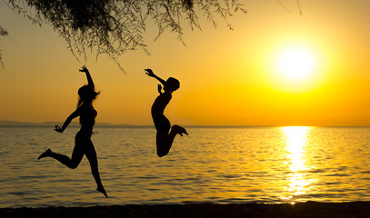 Girl and boy silhouettes jumping on the beach at sunset