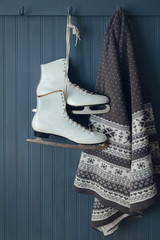 A pair of ice skates with blanket hanging on hook