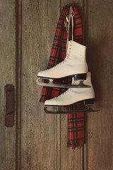 Ice skates with plaid scarf hanging on door