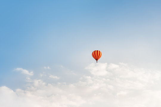 Lonely hot air balloon floating on the sky above the clouds