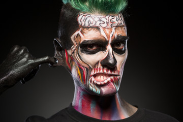 Skull face art, portrait of man with bright mystical makeup. Zombie mask on mans face isolated in black background.