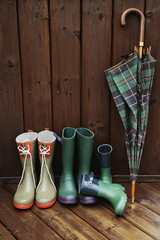Rain boots with plaid umbrella on back porch
