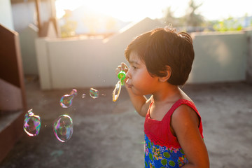Little girl blowing bubbles at sunset