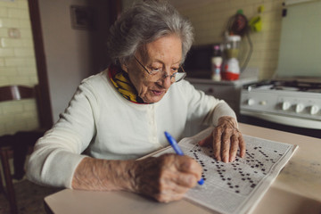 Old woman solving crossword puzzles in the kitchen