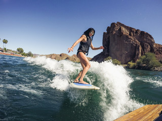 Woman Wakesurfing with Rock Cliff Background