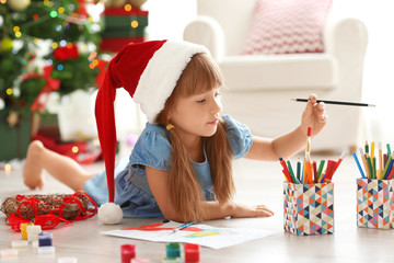 Cute girl drawing picture for Christmas on floor