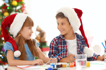 Cute children painting pictures for Christmas at table