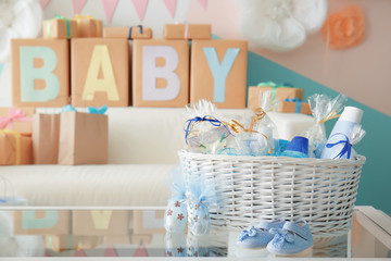 Wicker basket with gifts for baby shower party on table indoors