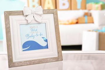 Framed greeting card for baby shower on blurred background