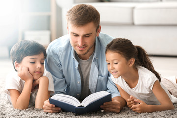 Young man and his little children reading book at home