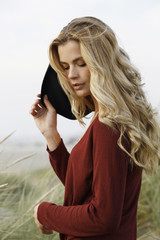 young woman with hat in dunes