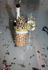 A bottle of champagne with a glass and a golden pineapple with happy new year headband